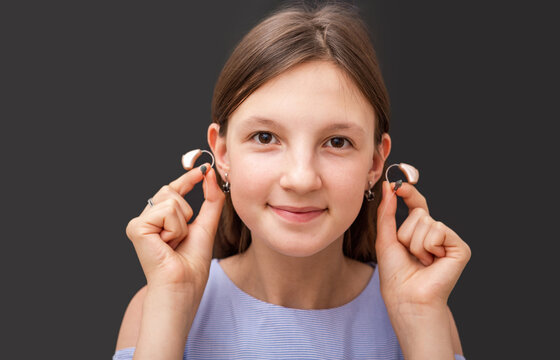 Teenage girl showing her modern hearing aids, close-up on a black background. Selection of hearing aids for a child