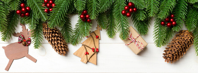Wall Mural - Top view of fir tree and New Year decorations on wooden background. Banner Christmas concept with copy space