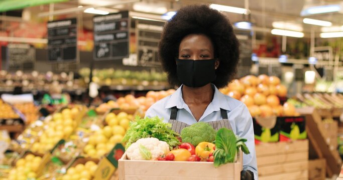 Close up of African American beautiful woman assistant in black mask standing in food store with vegetables. Female seller in apron holding different food in supermarket indoor. Quarantine concept