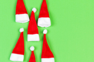 Wall Mural - Top view od stylish red Santa hats on colorful background. Merry Christmas concept with copy space