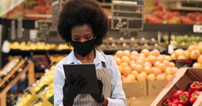 Close up portrait of African Americn beautiful female worker in black mask and gloves standing in supermarket and tapping on tablet. Woman manager browsing on device in grocery shop. Retail concept