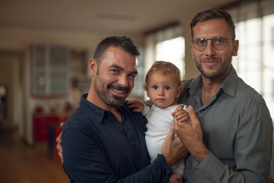 Authentic shot of young happy homosexual male gay family with adopted son toddler baby boy is smiling in camera in a kitchen at home.