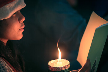A children singer hands holding candle and book with singing carol song on celebration of christmas...
