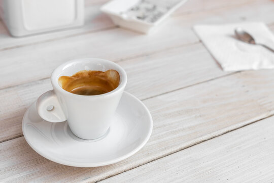 Warm tasty rich italian black espresso coffee cup in white mug on vintage biege wooden rerto style table at cafe or restaurant. Good morning breakfast drink concept. Urban city lifestyle