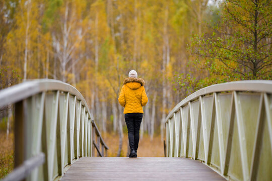 One young adult woman in yellow jacket slowly walking on bridge at natural park in colorful autumn day. Spending time alone in nature. Peaceful atmosphere. Back view.