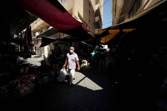A man wearing a face mask carrying a shopping bag walks in a local Souq (traditional market), following the outbreak of the coronavirus disease (COVID-19), in Manama, Bahrain