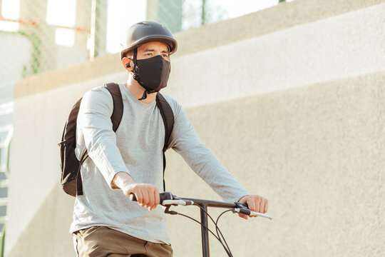 Cyclist man wearing face mask in the city. Concept of bicycles as a safer form of transportation during the New Normal