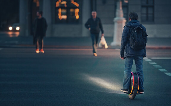 Man riding fast on electric unicycle through crosswalk at night with diode lights. Mobile portable individual transportation vehicle. Night riding, man on electric mono-wheel riding fast (EUC)