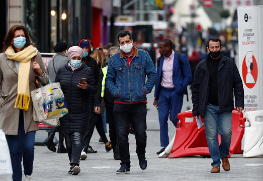 People wearing protective masks walk in a shopping street amid the coronavirus disease outbreak in Brussels