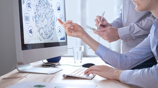 Data analysts working on data analytics and visualization with machine learning on computer screen in modern office. Data science in business, finance and innovation.