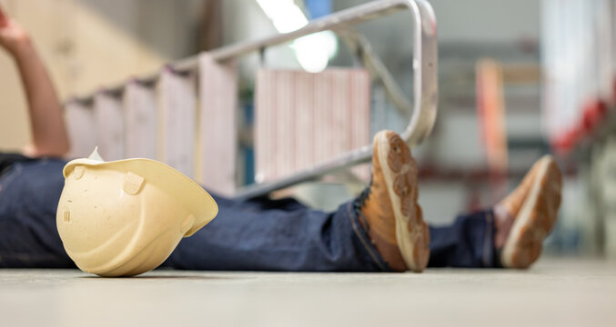 Male body lying on the floor after a work accident. Fallen ladder and safety helmet lying next to the body.