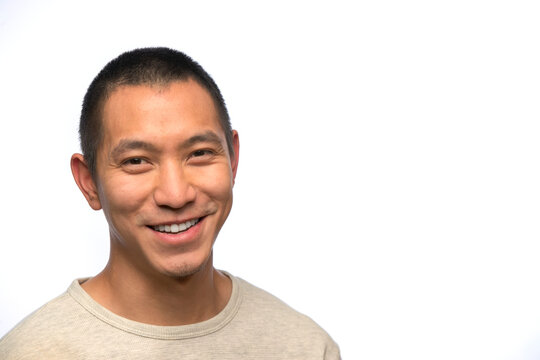 Portrait of young man of Asian descent with smirk on white background