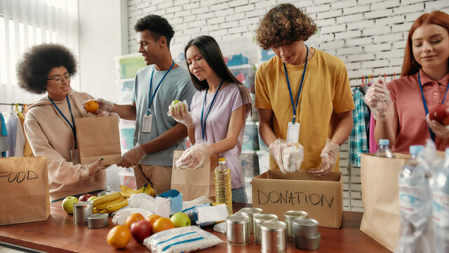Young male and female volunteers packing food and drinks donation for homeless into boxes and paper bags, Small group of people working in charitable foundation