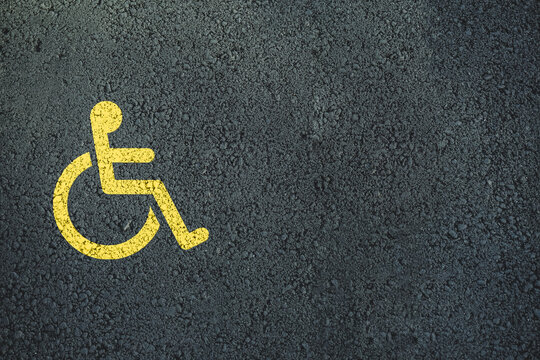 Yellow Handicap Sign Painted on Dark Asphalt.
