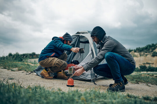Two men crouching near tent on rainy weather and preparing coffee. Camping trip concept.
