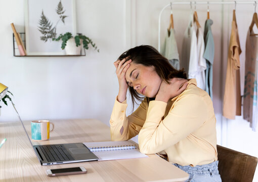 Tired businesswoman with headache and neck pain sitting at table while working from home