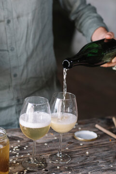 Midsection of man pouring wine in glass while preparing cocktail