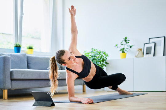 Woman learning side plank exercise on internet through digital tablet