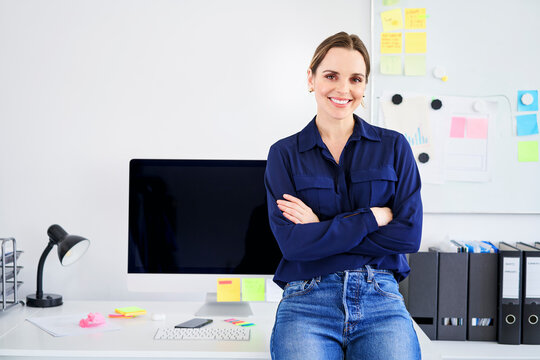 Confident creative businesswoman sitting with arms crossed on desk in office