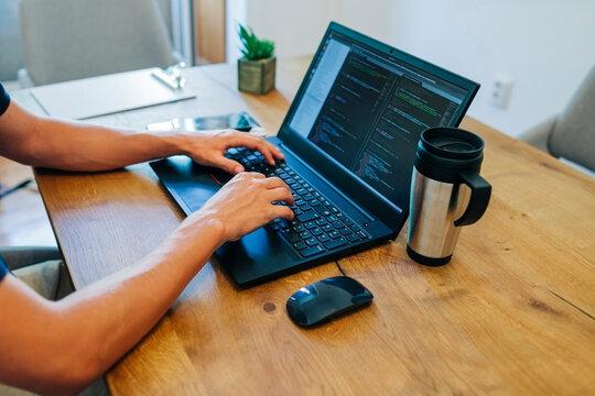 Male web designer programming through on laptop at desk in office