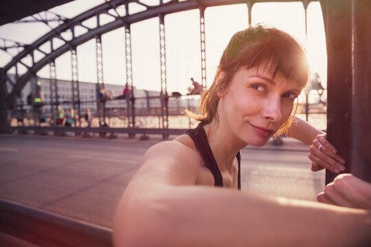 Beautiful woman looking away while exercising on bridge at sunset