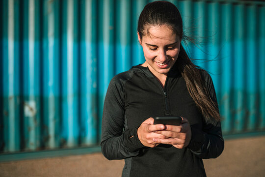 Athletic woman using smartphone in industrial park
