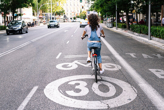 Mature woman riding on bicycle lane in city