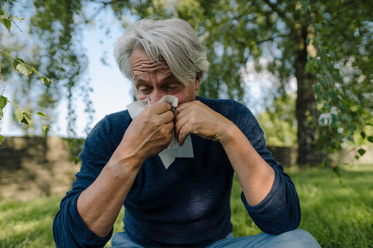 Wrinkled man blowing nose while sitting in field