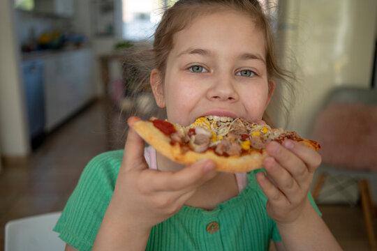 Cute girl eating slice of pizza at home