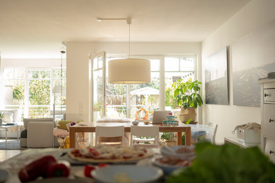 Living room with dining table against door and window during sunny day