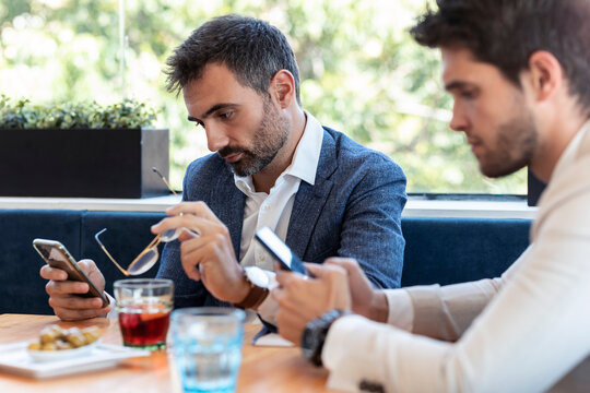 Male coworkers using smart phones in restaurant