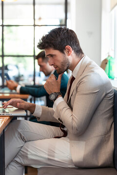 Businessman thinking while using laptop in restaurant