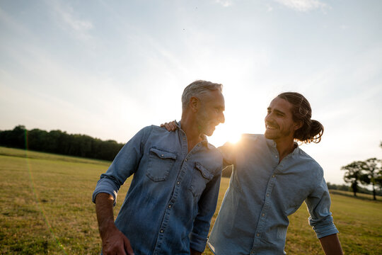 Happy father with adult son on a meadow in the countryside at sunset