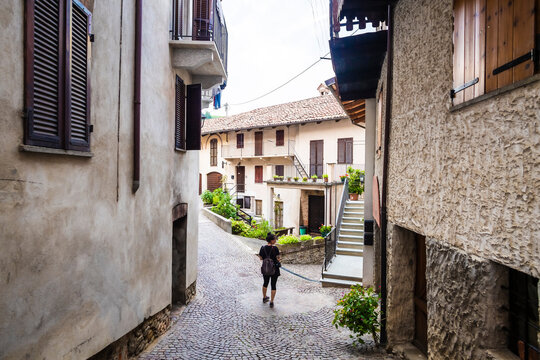 Italy,ÔøΩPiedmont, Female tourist standing in middle of cobblestone alley in old rural village