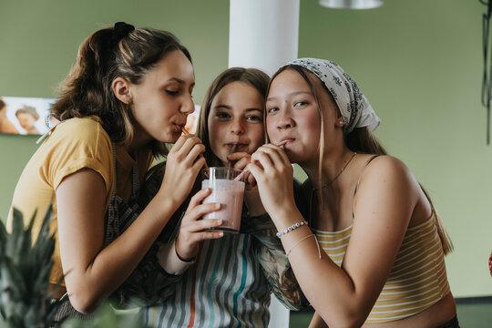 Teenage girls standing in kitchen sharing fresh fruit smoothie with drinking straws