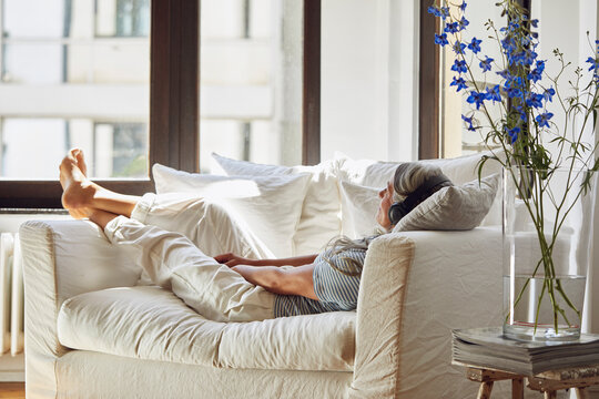Smiling woman listening to music on sofa in living room