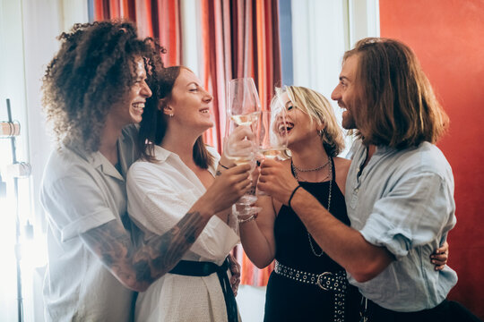 Cheerful male and female friends toasting wineglasses during party at home