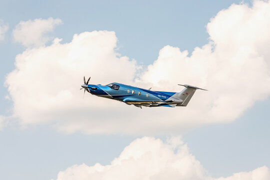 PRIBRAM, CZECH REPUBLIC - 12 August 2020. The Pilatus PC-12 NGX torboprop aircraft flies in the blue sky with clouds. The plane leaves from a small airport.