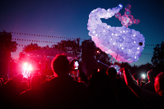 Whale made of purple balloons floating over crowd of people having fun during night music festival