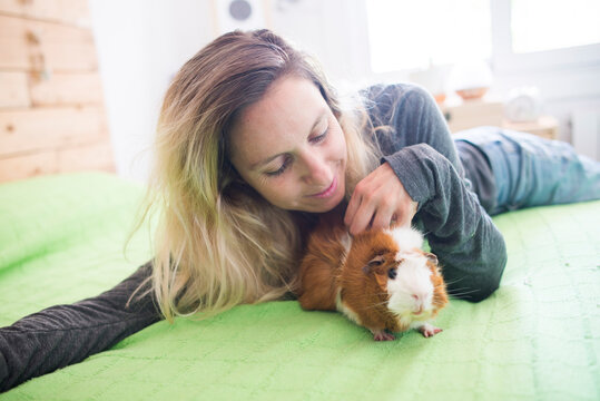 Woman stroking guinea pig while lying on bed at home