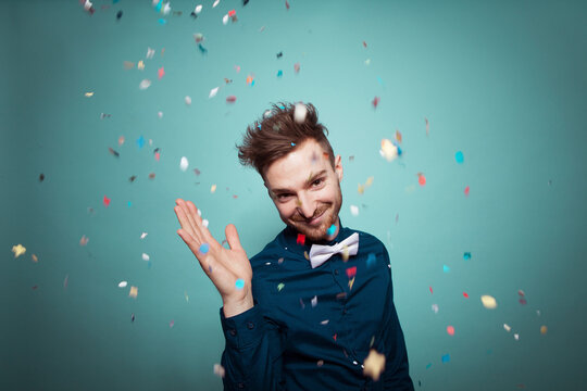 Portrait of young man throwing confetti