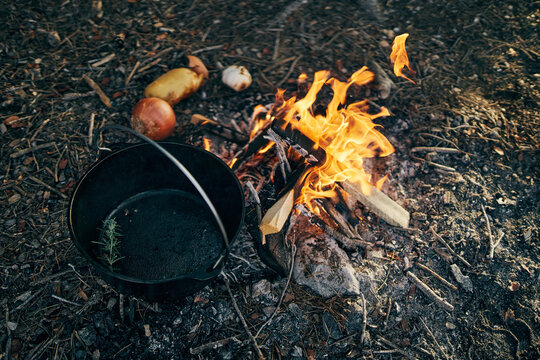 Cooking food over flames from campfire