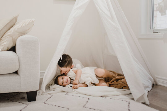 Brother whispering in sister's ear inside tent in living room