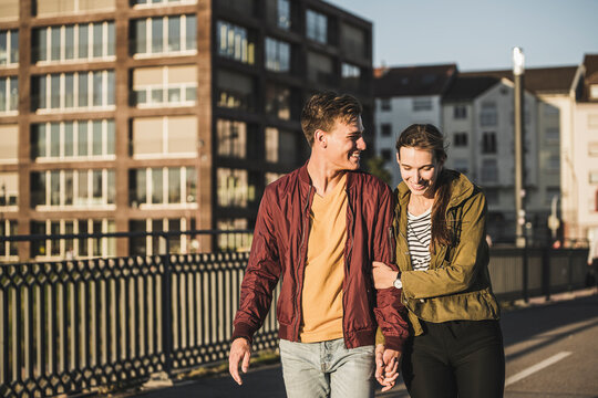 Smiling young couple holding hands while walking in city