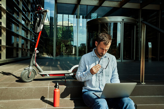 Entrepreneur with eyeglasses working over laptop while sitting on staircase
