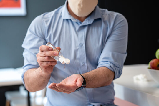 Businessman using hand sanitizer for disinfection at creative office cafeteria