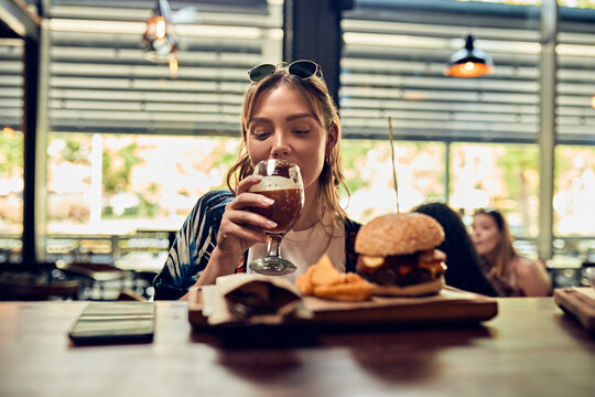 Woman having a beer and a burger in a pub