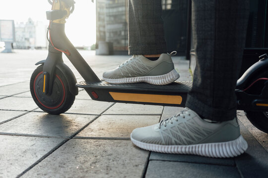 Low section of male entrepreneur wearing sports shoes while riding electric push scooter at downtown