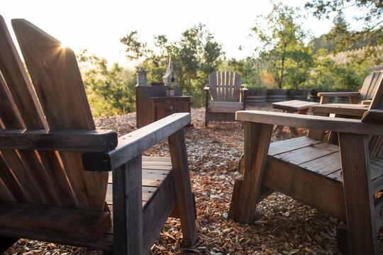 Wooden Adirondack chairs in vineyard during sunrise