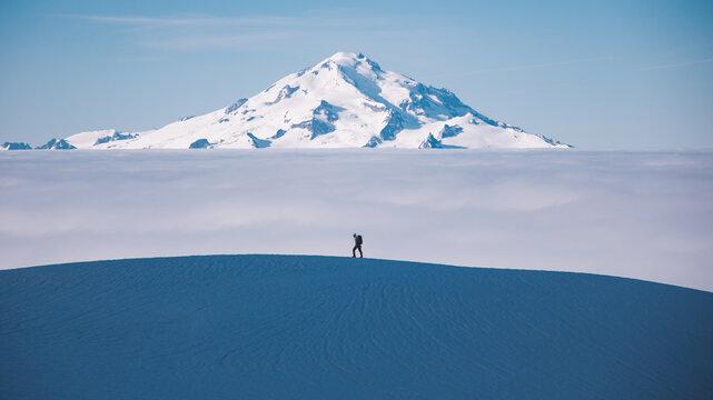 Man hiking on Dome Peak with Glacier Peak in background